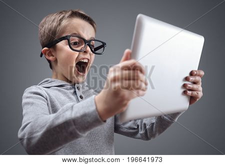 Shocked and surprised boy on the internet with digital tablet computer concept for amazement, astonishment, making a mistake, stunned and speechless or seeing something he should not see