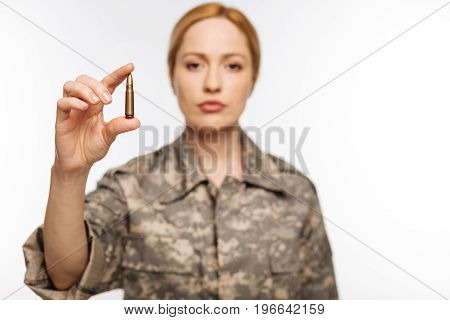 One shot to kill. Attractive ambitious experienced officer standing isolated on while background and demonstrating a shoot shell
