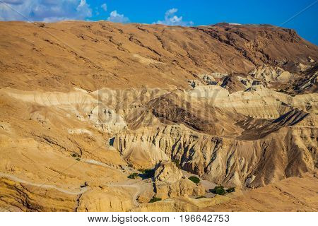 Dry ancient mountains in the vicinity of the Dead Sea. Bright hot summer day. At the bottom of the canyon are several green trees. The concept of extreme tourism