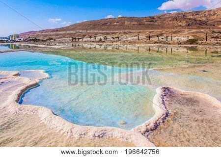 Summer, Israel. Very salty water in the Dead Sea glows with turquoise light. The evaporated salt has developed into fantastic patterns. The concept of ecological and medical tourism