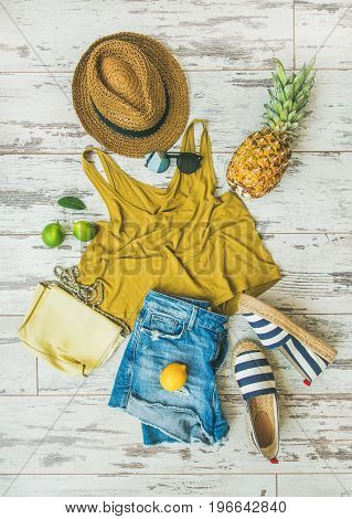 Colorful summer fashion outfit flat-lay. Denim shorts, straw sun hat, yellow top, espadrillas, leather shoulder bag, sunglasses, pineapple, limes and lemon over pastel parquet background, top view