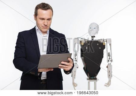 Lab tests. Talented expressive savvy specialist using his tablet for analyzing data he obtaining after running experiments on the robot