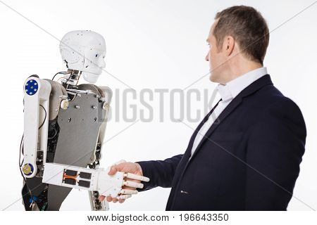 Do you understand politeness. Serious enthusiastic imaginative man shaking hands with a smart machine while tasting its abilities and standing isolated on white background