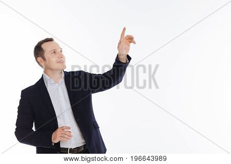 Look up. Observant neat handsome guy wearing stylish suit and posing isolated on white background while pretending touching some object
