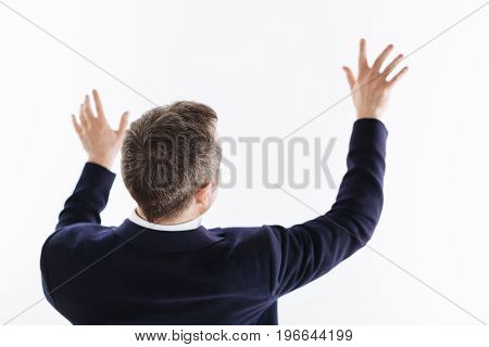 Using the hands. Talented handsome clever guy pretending touching something invisible while standing isolated on white background