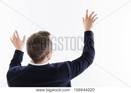 Holding in my arms. Inspired nice handsome man acting as if touching invisible object while standing isolated on white background