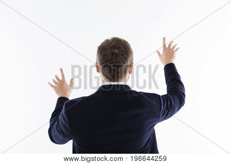 Maestro in action. Elegant passionate precise gentleman showing his back and standing isolated on white background and holding his hands up