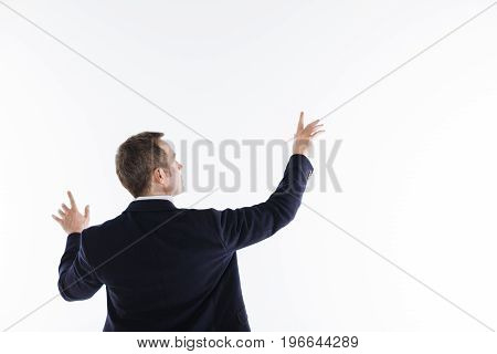Technological guy. Diligent smart progressive man wearing nice suit and standing isolated on white background while acting during the photoshoot