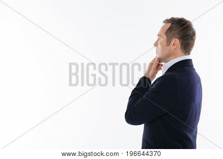 Thoughtful look. Committed focused handsome man seeming very interested while looking at something in the distance and posing isolated on white background