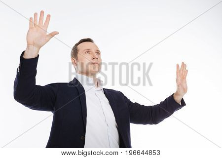 I will not fight. Handsome bright enthusiastic man acting during the photoshoot while holding his hands up and standing isolated on white background