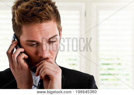 Worried businessman using a cell phone