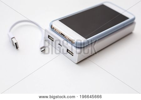 Smartphone and power bank concept over white