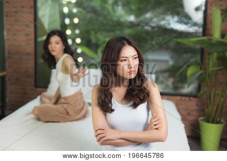 Two Friends Not Talking To Each Other After Fight On Bed In Sitting Room At Home
