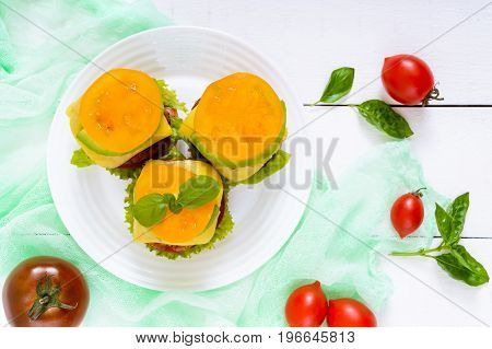 Sandwiches (burgers) with yellow and black tomatoes juicy cutlet avocado on a plate on a white wooden background. Top view.