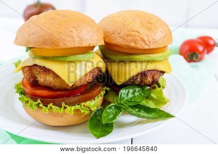 Sandwiches (burgers) with yellow and black tomatoes juicy cutlet avocado on a plate on a white wooden background.