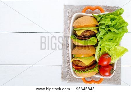 Sandwiches (burgers) with yellow and black tomatoes juicy cutlet avocado on a white wooden background. The top view. Empty space for your notes and projects.