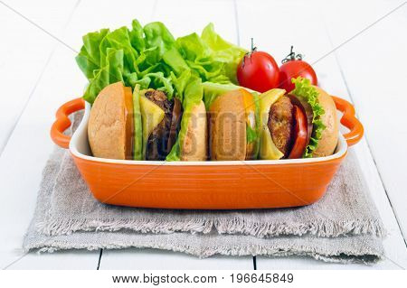 Sandwiches (burgers) with yellow and black tomatoes juicy cutlet avocado on a white wooden background.