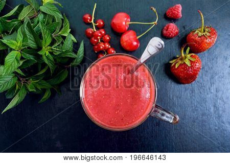 Berry smoothies in a glass mug on a black background. Top view.