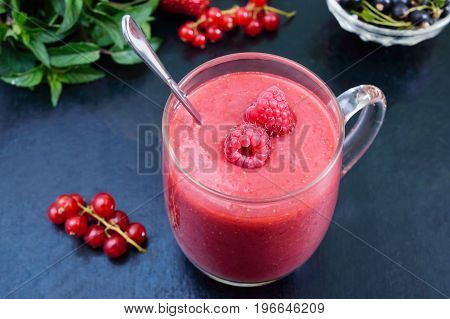 Berry smoothies in a glass mug on a black background.