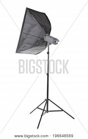 A modern gray softbox isolated over the white background. Professional electric equipment for photographers. A lighting stripbox with a flashlight on a tall tripod. Photographic accessory.