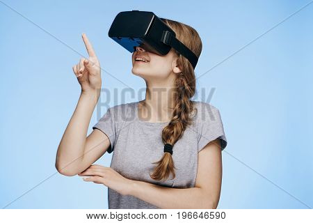 Young beautiful woman on a blue background with virtual reality glasses.