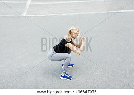 Burn in buttocks. Side view of young woman in sportswear doing squat . Young beautiful woman squats