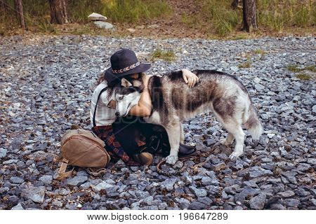 Side view of trendy girl sitting on rocky ground embracing Husky dog.