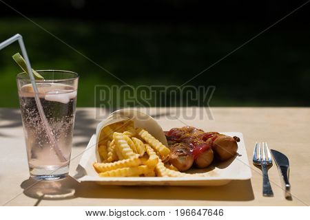Currywurst and pommes on recyclable dishes, dinner