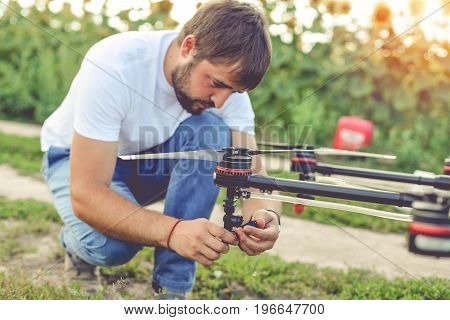Young engineer preparing agriculture drone before flying on the sunflower field.