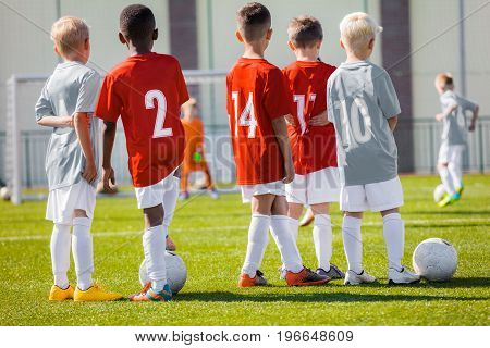 Children Sport Soccer Youth Team. Football Soccer Game For Children. Kids Soccer Players Watching Tournament Game. Penalty Game in the Background
