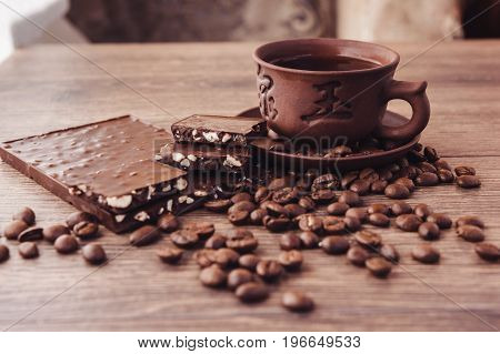 roasted coffee beans with chocolate and nuts on a wooden surface. can be used as a background
