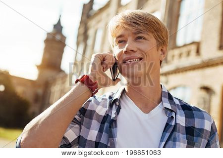 Pleased guy. Emotional clever enthusiastic gentleman attending classes and taking the moment to answer a phone call from his friend
