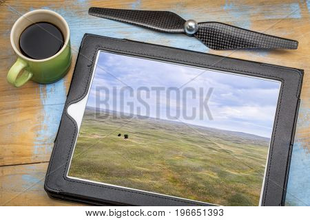 landscape of Nebraska Sandhills with two lonely trees, reviewing aerial image on a digital tablet with a cup of coffee