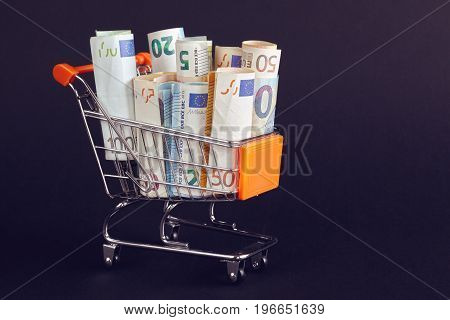 Shopping Cart Filled With Euro Bill Rolls.