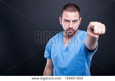 Male Medical Nurse Pointing Camera Being Serious