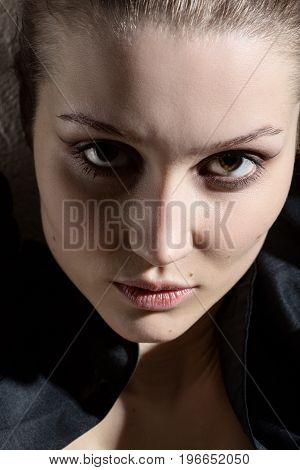 serious luxury woman with natural beauty makeup looks at camera