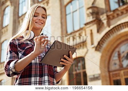 Social interaction online. Young savvy original girl using free wifi while walking around the campus and waiting for her next lecture