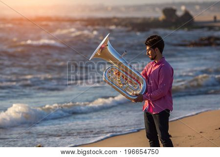 Young man with trumpet on the sea coast during surf. Tuba instrument.