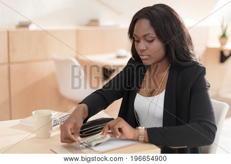 Beautiful African American Woman Paying For Coffee With Cash In Cafe