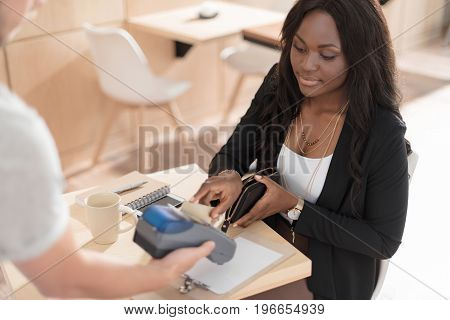 Attractive African American Woman Paying With Credit Card Through Terminal In Cafe