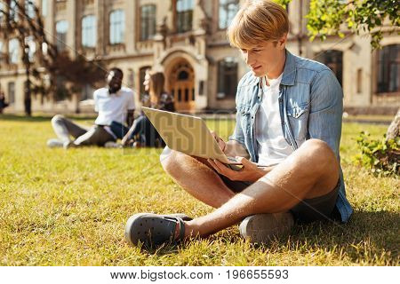 Fresh thoughts on fresh air. Committed clever diligent guy enjoying nice weather while sitting on the grass before campus an reading something on his laptop