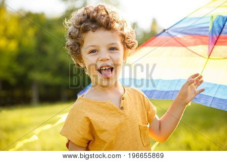 Young curly haired boy wearing orange shirt putting out tongue holding kite looking away.