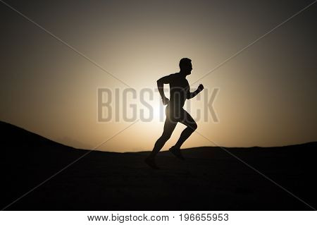 man runner. silhouette of running man on sunset fiery sky background in mountain sport and recreation future and success people and nature speed and healthy lifestyle