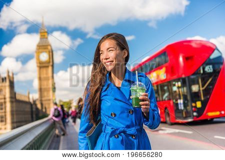 Healthy London urban city business woman drinking green detox smoothie walking on Westminster Bridge with Big Ben, red double decker bus background, London Europe destination, England, Great Britain