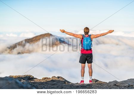 Success winner fitness man reaching top of mountain peak winning with open arms in freedom. Hiker or trail running runner successful in goal challenge.