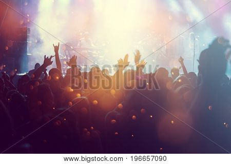 Photo of many people enjoying concert, crowd with raised up hands dancing in nightclub, audience applauding to musician band, night entertainment, music festival.