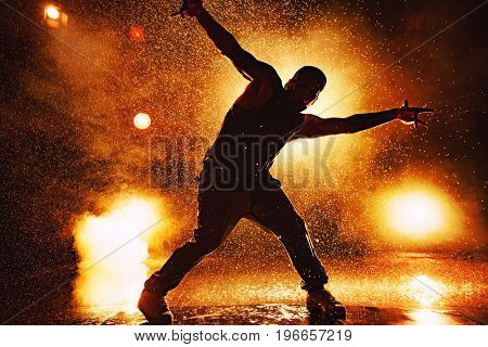 Young man break dancer dramatic silhouette standing in club with lights and water. Tattoo on body.