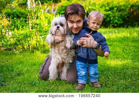 Father with son and dog together portrait in summer green garden