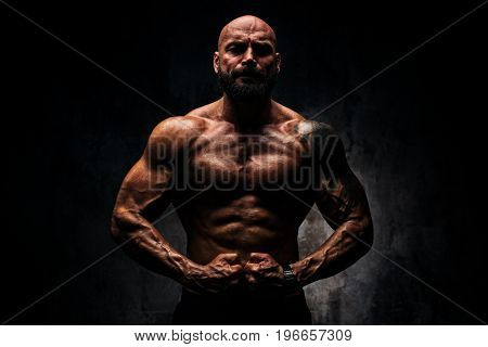 Strong man bodybuilder on dark background. Dramatic colors. Tattoo on body.