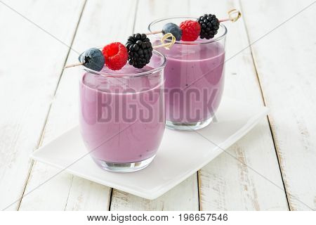 Healthy berry smoothie in glass on white wooden table